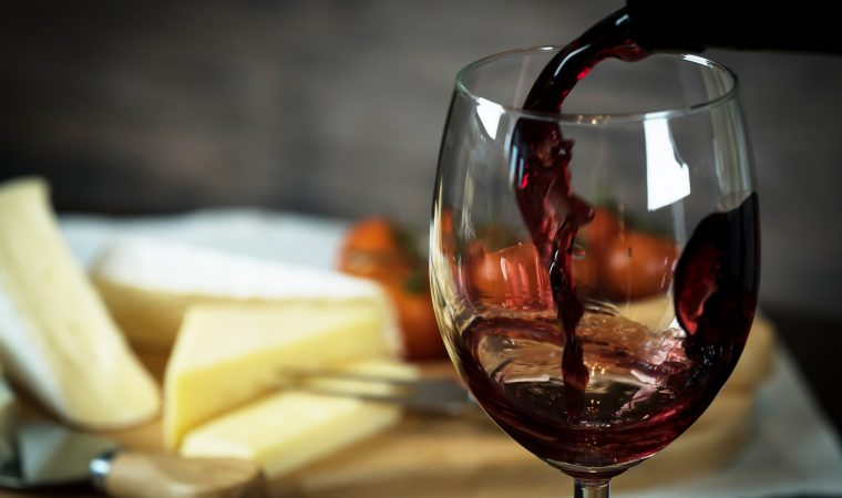 pouring red wine and cheese variety